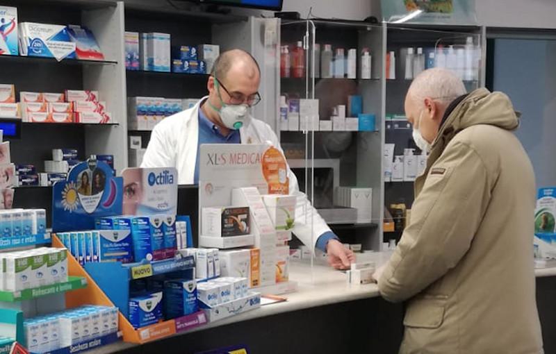 Farmacista che usa Pharmashield e mascherina contro Covid-19